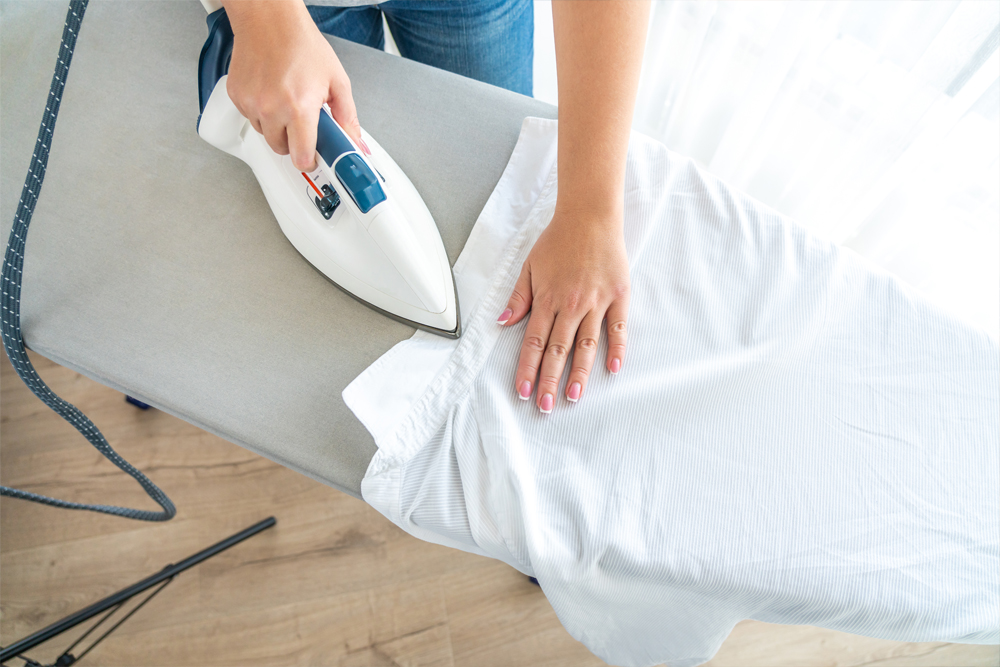 Top view of woman ironing white shirt collar on ironing board